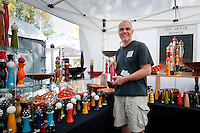 Robert Wilhelm poses in his booth, filled with bright-colored pepper mills during the 23rd Annual Downtown Naples Festival of the Arts, hosted by The von Liebig Art Association and Downtown Association, Naples, Florida, USA, March 26, 2011. Photo by Debi Pittman Wilkey