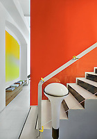 A modern staircase with a glass side panel is separated from a living area by a vibrant orange wall.