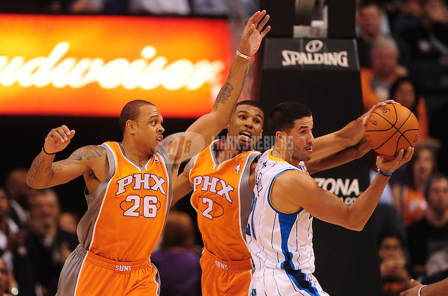 Dec. 26, 2011; Phoenix, AZ, USA; Phoenix Suns players Shannon Brown (left) and Ronnie Price (center) defend against New Orleans Hornets guard Greivis Vasquez at the US Airways Center. The Hornets defeated the Suns 85-84. Mandatory Credit: Mark J. Rebilas-USA TODAY Sports