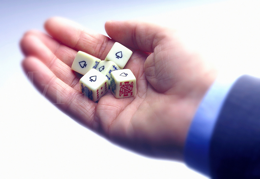 Hand of businessman holding poker dice showing five aces.