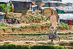 A Rohingya woman walks along a path in the Mainerghona Refugee Camp near Cox's Bazar, Bangladesh, on October 27, 2017. Since August more than 600,000 Rohingya have fled government-sanctioned violence in Myanmar for safety in Bangladesh.
