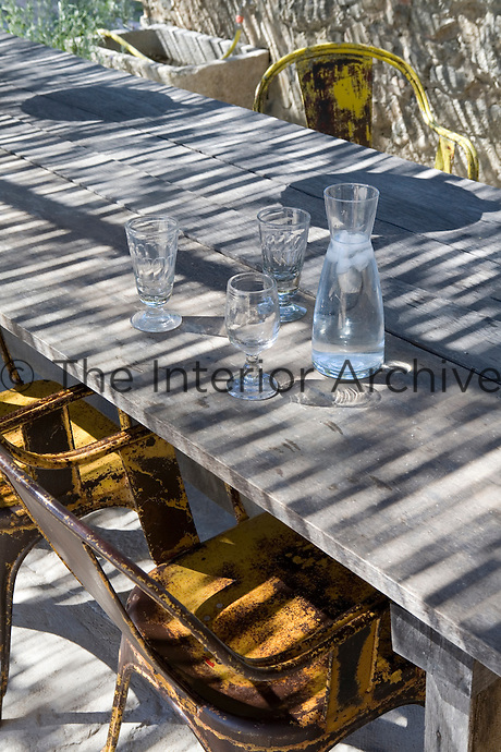 A canopy of woven reeds throws textured shadows across a shared outdoor dining area of a rural Spanish stone house