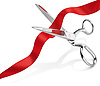 Metal scissors cutting a red ribbon, on a white background