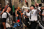 A police officer is giving instructions to Protestors during a weekly march called by every friday on Wall Street in New York, United States. 23/03/2012.  Photo by Kena Betancur / VIEWpress.