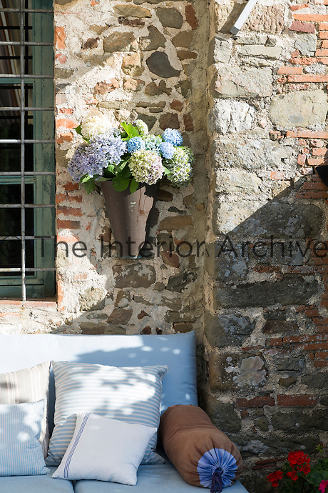 A wall planter filled with hydrangea blooms hangs above a sofa on the outdoor terrace.