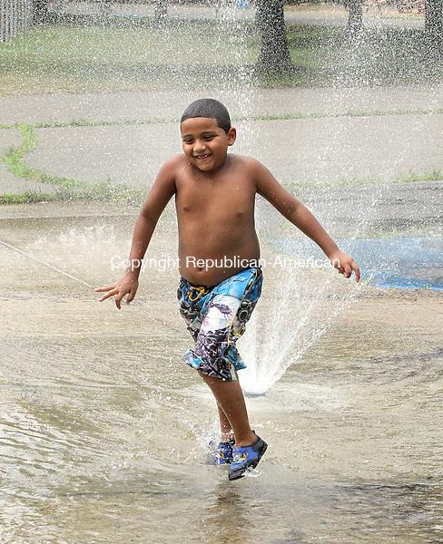WATERBURY CT.-15  JULY 2010-071510DA02- Elyjah Alcaraz, 6 of Waterbury runs through a sprinkler to cool of Thursday at Bucks Hill Park in Waterbury.<br /> Republican-American Darlene Douty