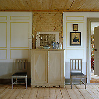 Two antique chairs flank a cupboard of lime-washed wood in the dining room of this country house