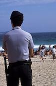 Rio de Janeiro, Brazil. Policeman guarding the beach; people; sea.