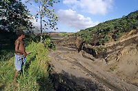 Young boy looking at the gully done by the water of the former siwi lake, Sulphur Bay, Tanna Island, Vanuatu