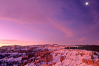 730750114 sunrise lights up the hoodoos covered in snow on a cold winter morning with the moon above in bryce canyon national park utah