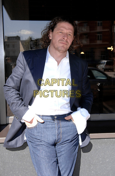 MARCO PIERRE WHITE.Pictured outside his new restaurant in Stamford Bridge, Chelsea, London, England..September 18th, 2007.chef half length stubble facial hair blue black jacket white shirt hands in pockets leaning 3/4 jeans denim   .CAP/DH.©David Hitchens/Capital Pictures.
