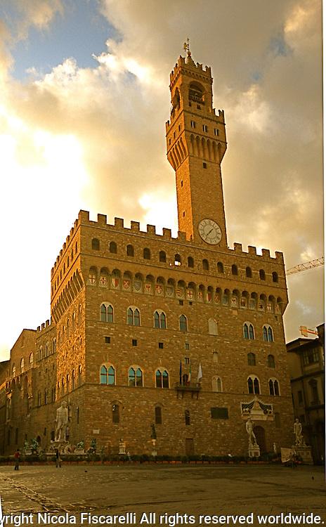 Early morning sun illuminates the walls of Palazzo Vecchio in the beautiful city of Florence Italy.