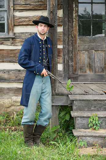 Soldier standing and posing with pistol, American Civil War Union infantry private by period log house.