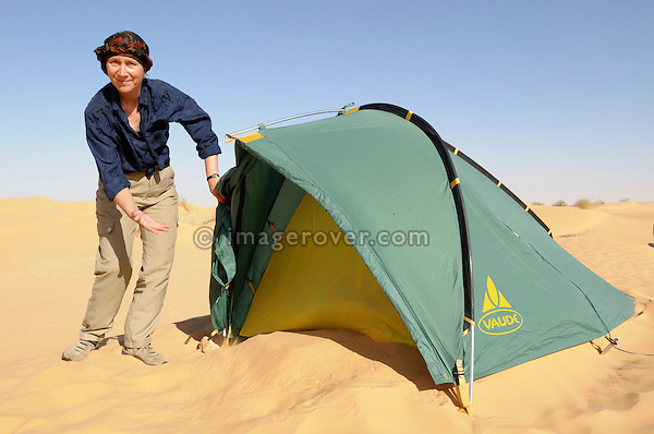 Africa, Tunisia, nr. Ksar Rhilane. Desert tourist Doris pointing out all the sand that after a windy night has piled up in front of her small tent. --- No releases available, but releases may not be needed for certain uses. --- Info: Image belongs to a series of photographs taken on a journey to southern Tunisia in North Africa in October 2010. The trip was undertaken by 10 people driving 5 historic Series Land Rover vehicles from the 1960's and 1970's. Most of the journey's time was spent in the Sahara desert, especially in the area around Douz, Tembaine, Ksar Ghilane on the eastern edge of the Grand Erg Oriental.