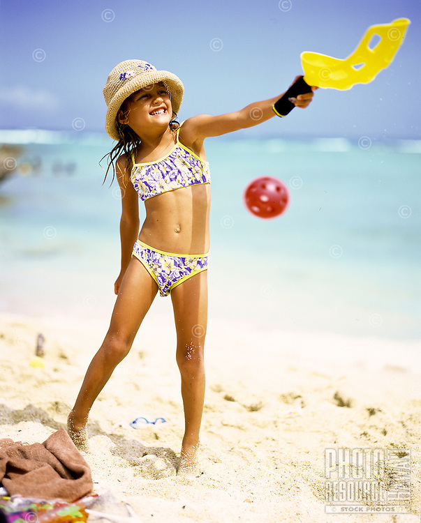 Small girl in bikini and hat plays with beach toys.