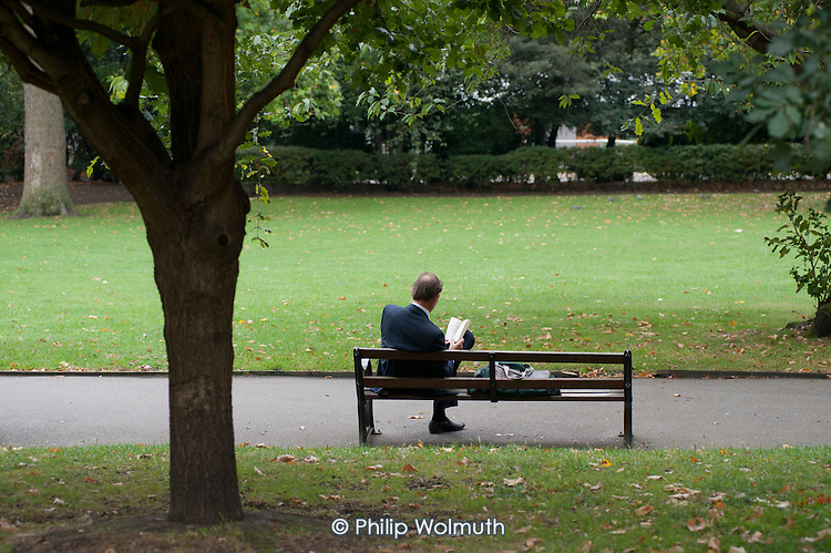 A man reading a book on a park bench in Lincoln's Inn Fields, London.