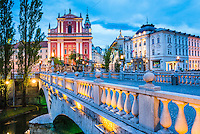 Ljubljana at night. Franciscan Church of the Annunciation seen from one of the Triple Bridges (Tromostovje), Ljubljana, Slovenia, Europe
