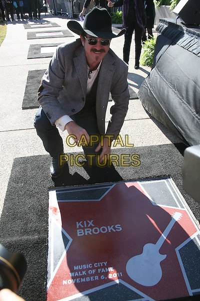 Kix Brooks received his star on the Music City Walk of Fame, inducted by Reba McEntire, Nashville, Tennessee, USA..November 6th, 2011.full length grey gray suit jacket black hat kneeling jeans denim.CAP/ADM/BEV.©Bev MoserAdMedia/Capital Pictures.