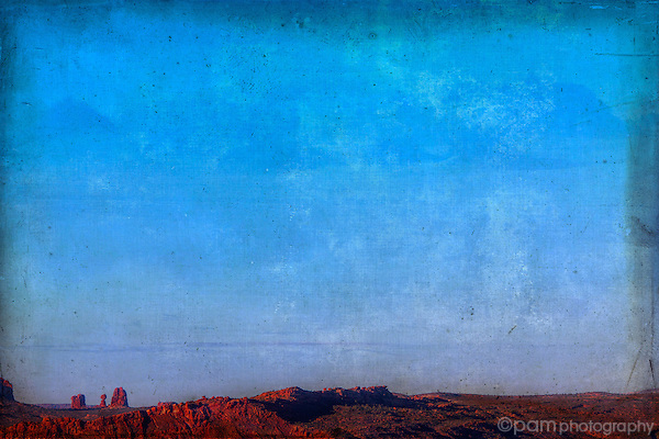 Textured image of Utah's red rocks with expansive blue sky.