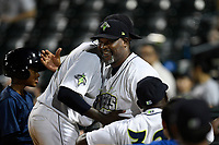 Tony Dibrell (8) of the Columbia Fireflies, left, is congratulated by pitching coach Jonathan Hurst during a game against the Charleston RiverDogs in which he set a Fireflies single-season strikeout record of 138 on Tuesday, August 28, 2018, at Spirit Communications Park in Columbia, South Carolina. Columbia won, 11-2. (Tom Priddy/Four Seam Images)