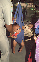 Indonesia; Java, baby during the posyandu (training program for the health of children),control of the weight of the newborn .<br /> Indonesia, Giava,  bambino durante il posyandu (centri sanitari per la salute dei bambini), controllo del peso del neonato.