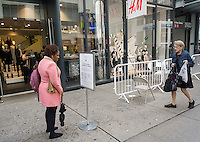 A woman reads the wristband rules outside of an H&M store in New York selling their Balmain x H&M collboration on Thursday, November 5, 2015. The collection, designed by the young head of Balmain, Olivier Rousteing, was highly anticipated by fashionistas and drew crowds around the world. In New York H&M instituted a wristband system to time when shoppers could arrive to control crowds. (© Richard B. Levine)