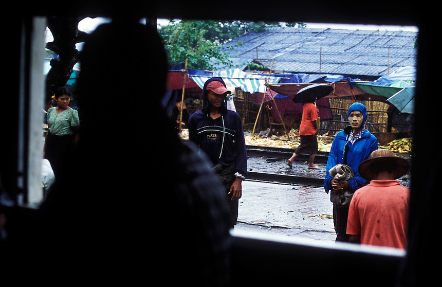People wait in the rain for a suburban train, Yangon, Burma, 2006.