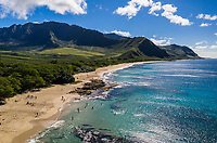 Beachgoers enjoy Makua Beach and Bay, West O'ahu, seen from above on a sunny day.