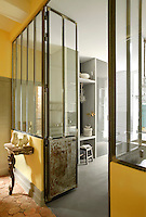 Access to a contemporary kitchen is through iron-framed glass doors
