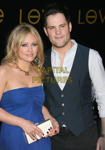 "HILARY DUFF & MIKE COMRIE.Cartier's 3rd Annual ""Love Day"" Celebration at a Private Residence in Bel Air, Los Angeles, California, USA..June 18th, 2008.half length blue strapless dress white clutch bag waistcoat trousers couple gold necklace white clutch bag .CAP/ADM/MJ.©Michael Jade/AdMedia/Capital Pictures."