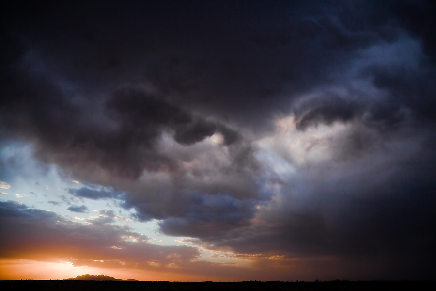 Classic Big Sky weather in Central Australia. A storm moves through as the sun lowers behind Kata Tjuta producing a dramatic scene.
