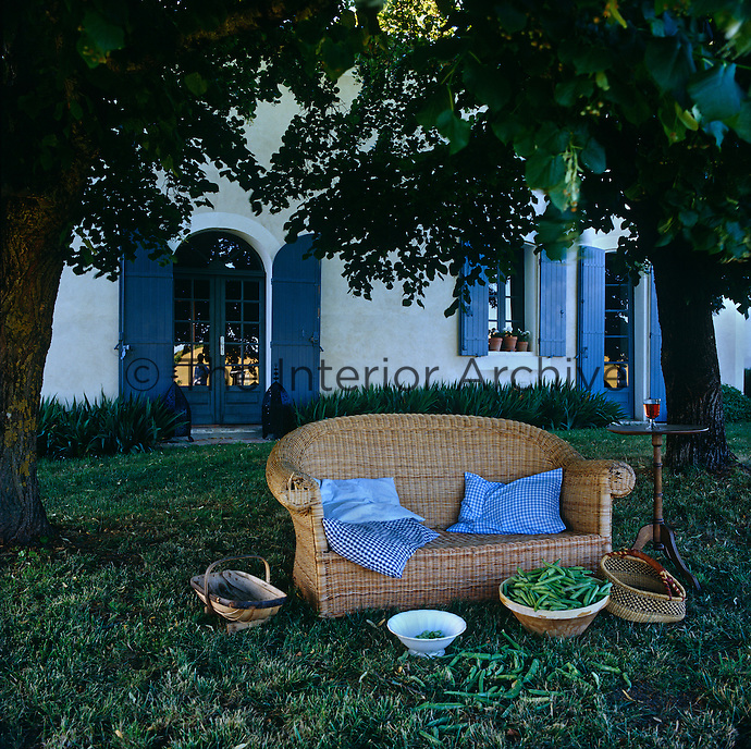 A wicker armchair under a shady tree in the garden immediately outside the house