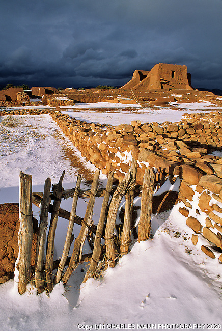 The adobe ruins of Pecos National Monument near the village of Pecos, New Meixco, lie covered with a fresh snowfall as the clouds of a winter storm retreat.
