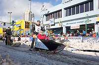 Peter Kaiser and team leave the ceremonial start line with an Iditarider at 4th Avenue and D street in downtown Anchorage, Alaska during the 2015 Iditarod race. Photo by Jim Kohl/IditarodPhotos.com