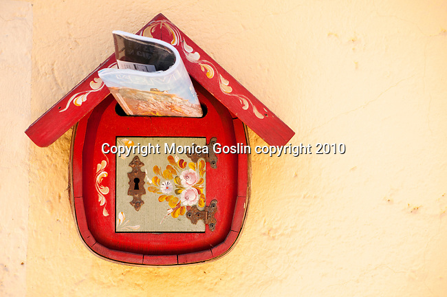 Red mailbox with painted flowers in Sala Comacina, a town on Lake Como, Italy