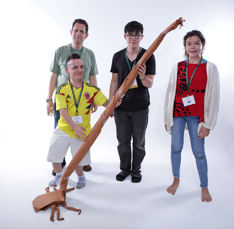 New York, NY, USA - June 24, 2018: Scenes from the Big Folding event at the annual OrigamiUSA Convention. Featured in this picture left to right: Diego Becerra, Columbia, Jorge Jaramillo, Columbia, Enzo Lee Solano (first timer), Australia, Kika Salgo, NY. Model: Giraffe beetle.