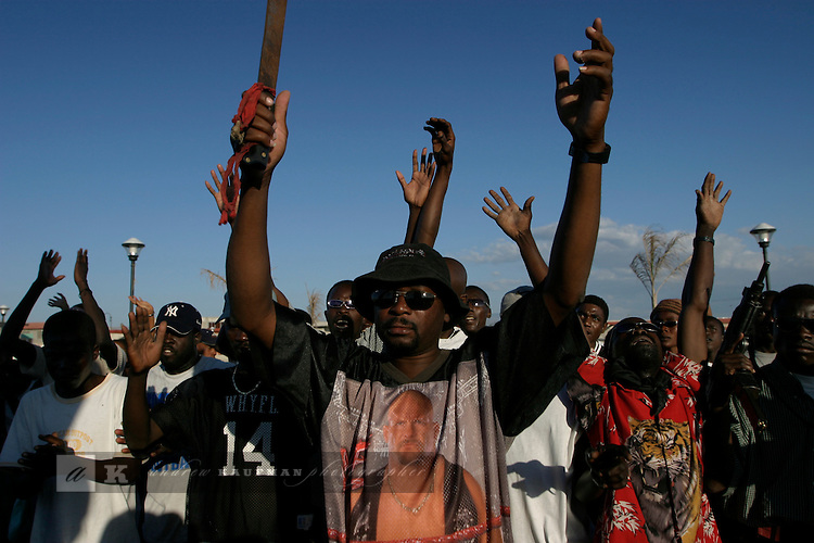 February 16, 2004. Gonaives, Haiti. The People for the Liberation of Haiti in Gonaives march for freedom. Rebels hold this northern city of Gonaives after Anti-Aristide  forces drove away the police and mayor. Butteur with the machete is a rebel leader and leads the citizens of Gonaive in their daily manifestation.