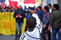 CORTEO IN DIFESA DEI MIGRANTI NELLA FOTO UN BAMBINO FILMA IL CORTEO CRONACA BRESCIA 28/03/2015 FOTO MATTEO BIATTA