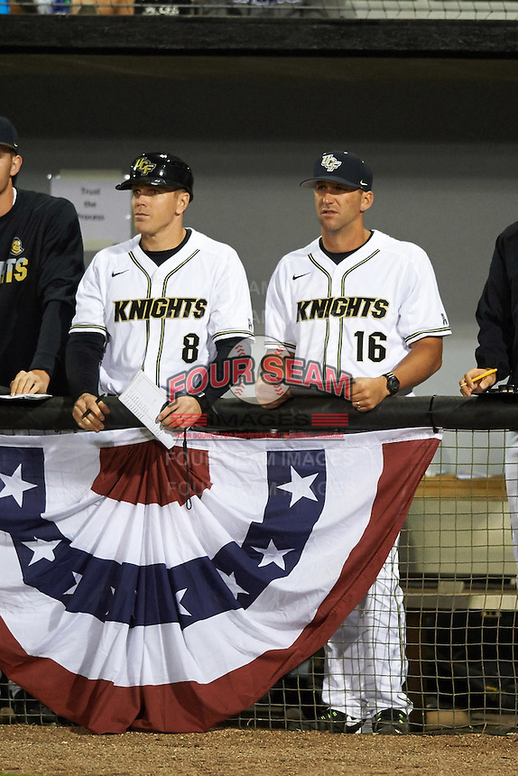 UCF Knights coaches Ryan Klosterman (8) and Justin Parker (16) in the dugout during a game against the Siena Saints on February 17, 2017 at UCF Baseball Complex in Orlando, Florida.  UCF defeated Siena 17-6.  (Mike Janes/Four Seam Images)