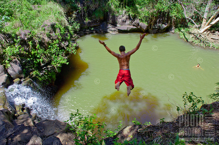 Boy jumping into pool at the base of a waterfall, Twin Falls, Haiku, Maui