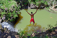 Boy jumping into pool at the base of a waterfall, Twin Falls, Haiku, Maui