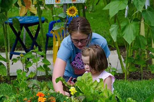 Young woman teaches girl in summer camp, Yarmouth Community Garden, Maine
