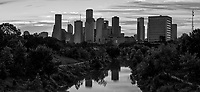 Houston Buffalo Bayou Skyline Pano BW -  This black and white Houston skyline pano at sunrise over the Buffalo Bayou in  downtown area. The city skyline also reflected on the water of the Buffalo bayou   Houston is a city of many skyscrapers and these are some of the taller one in the downtown part of the city from along the park over the bayou.