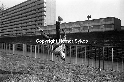 Girl turning cart wheels south Heygate Estate, Walworth, London estate UK 1980s.
