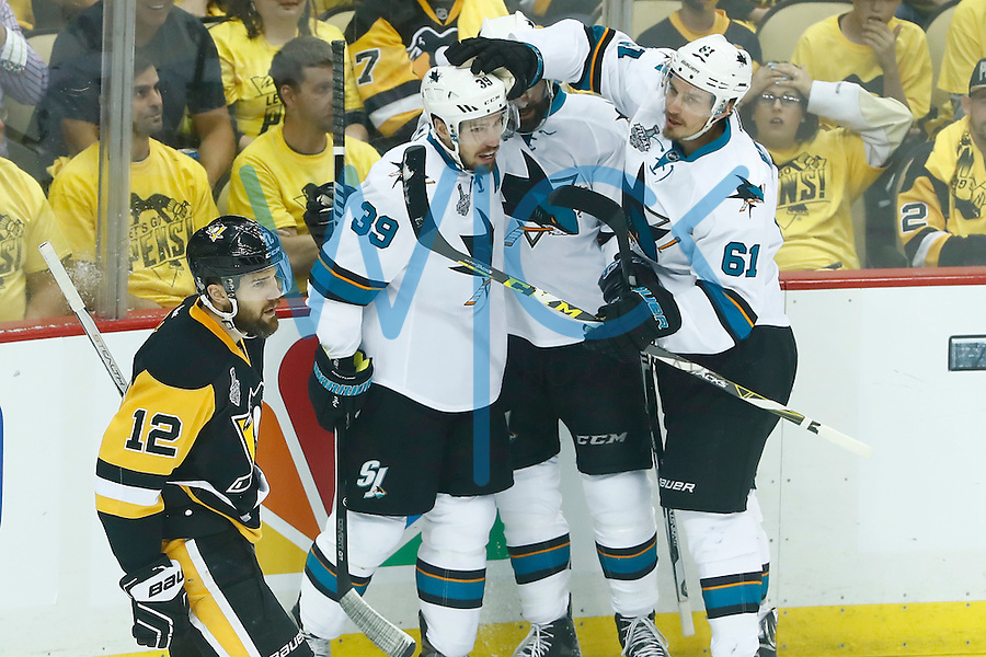 Logan Couture #39 of the San Jose Sharks is congratulated by teammates after scoring a goal in the first period against the Pittsburgh Penguins during game five of the Stanley Cup Final at Consol Energy Center in Pittsburgh, Pennsylvania on June 9, 2016. (Photo by Jared Wickerham / DKPS)