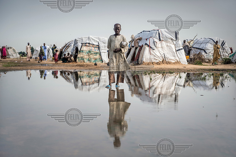 A child walks through a puddle in Muna Garage, a large IDP camp on the outskirts of Maiduguri where an estimated 50,000 people live. The camp's residents have fled regions occupied by Boko Haram but as the army retakes the territory more people arrive as they go in search for food following their liberation.