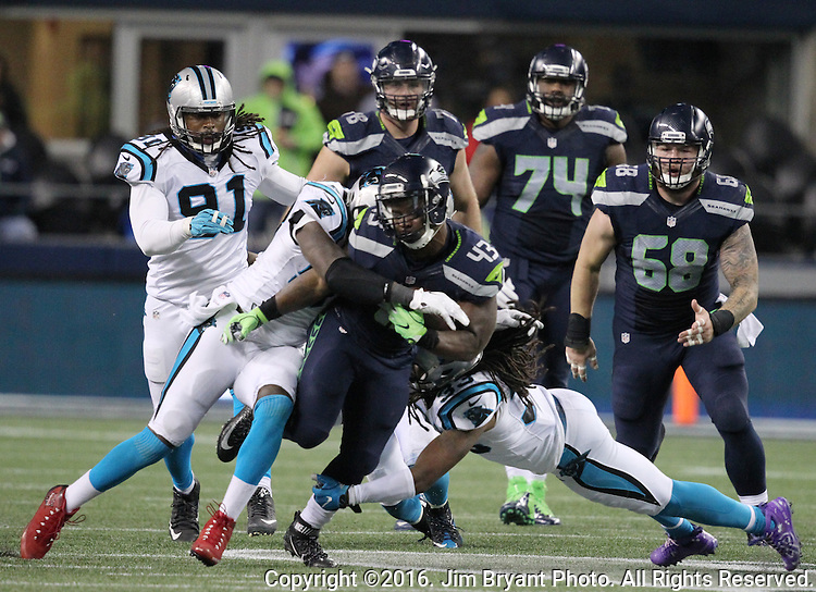 Seattle Seahawks running back Troymaine Pope (43) runs through the attempted tackles of Carolina Panthers free safety Michael Griffin (22) and free safety Tre Boston (33) at CenturyLink Field in Seattle, Washington on December 4, 2016.  Seahawks beat the Panthers 40-7.  ©2016. Jim Bryant photo. All Rights Reserved.