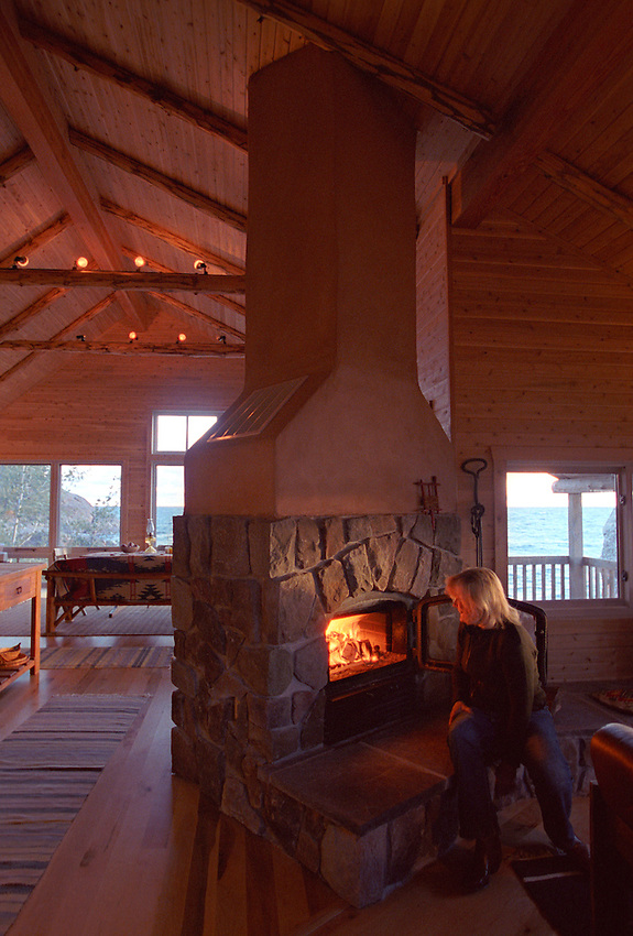 Phyllis Berg-Pigorsch fires up the custom fireplace in her Lake Superior cottage on Middle Island Point near Marquette, Mich.