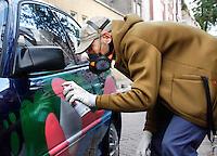 Man spuit graffiti op zijn auto