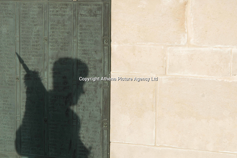 Pictured: A shadow of an ex serviceman on the memorial plaque Friday 11 November 2016<br /> Re: Remembrance Day service at the Cenotaph in Swansea, south Wales, UK.